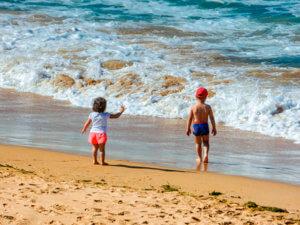 Dos niños en la playa durante un viaje con chicos
