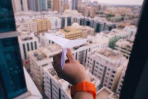 Pensando en viajes con un avión de papel sobre la ciudad