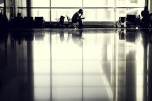 Hombre agarrándose la cabeza tras la cancelación de vuelos en una sala de espera